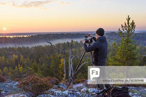 Mann Fotografie nehmen Sonnenuntergang