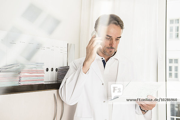 Male doctor reading a medical record and talking on a mobile phone  Munich  Bavaria  Germany