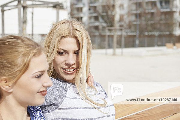 Two friends sitting on a bench in a playground  Munich  Bavaria  Germany