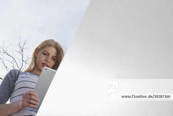 Low angle view of a teenage girl using a digital tablet  Munich  Bavaria  Germany