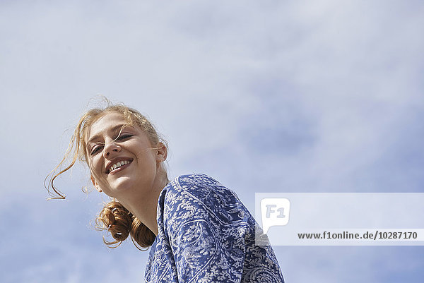 Low angle view of a young woman smiling  Munich  Bavaria  Germany