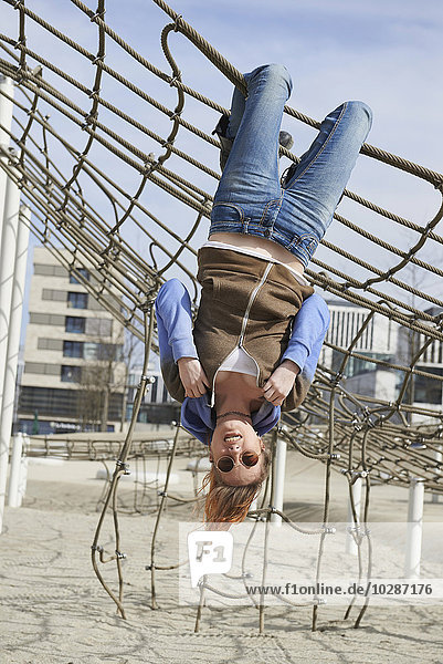 Young woman hanging from a climbing net in playground  Munich  Bavaria  Germany