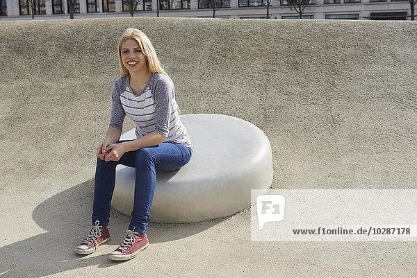 Teenage girl sitting on a round stone in playground  Munich  Bavaria  Germany