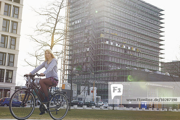 Teenage girl riding a bicycle in city  Munich  Bavaria  Germany