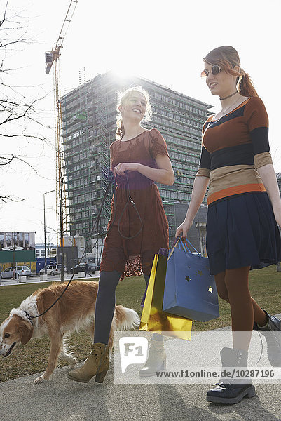 Two friends walking with dog  Munich  Bavaria  Germany