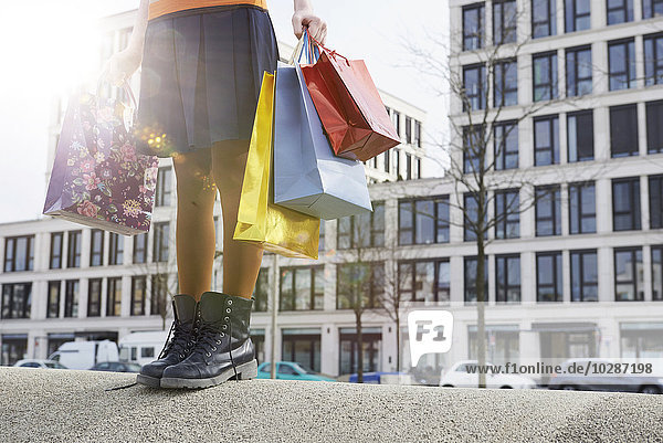 Low section view of woman holding shopping bags  Munich  Bavaria  Germany