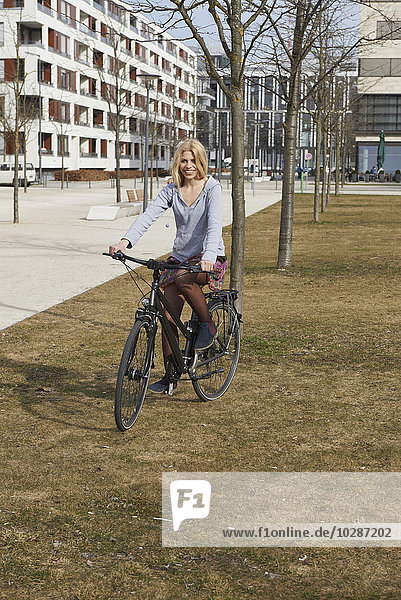 Teenage girl riding bicycle in a playground  Munich  Bavaria  Germany