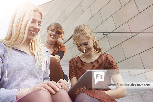 Three friends using a digital tablet and smiling  Munich  Bavaria  Germany