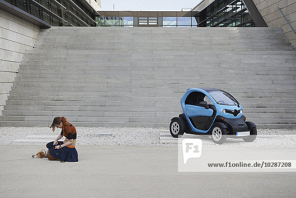 Young woman with dog and electric car in front of staircase  Munich  Bavaria  Germany