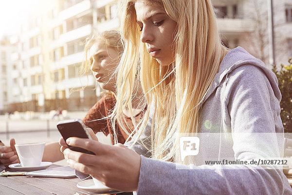 Teenage girl text messaging at sidewalk cafe  Munich  Bavaria  German