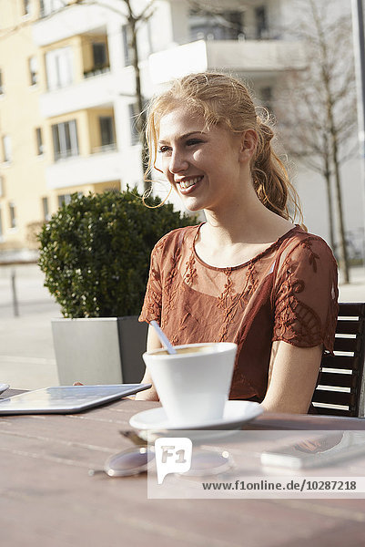 Young woman smiling at sidewalk cafe with digital tablet and coffee on table  Munich  Bavaria  Germany