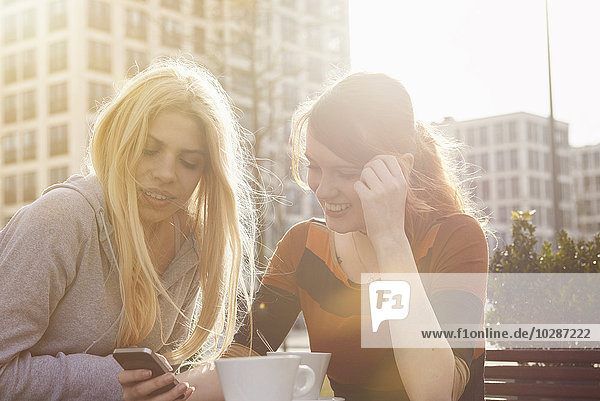 Two friends text messaging at sidewalk cafe  Munich  Bavaria  Germany