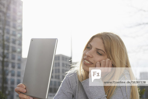 Teenage girl using a digital tablet and smiling  Munich  Bavaria  Germany