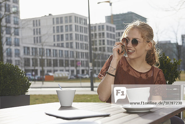 Young woman talking on a mobile phone at sidewalk cafe  Munich  Bavaria  Germany