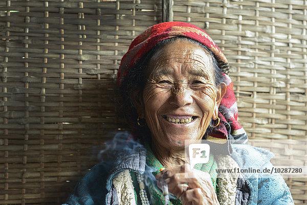 Portrait of a Nepali senior woman smoking and smiling  Nepal