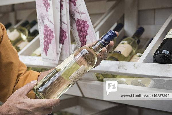 Customer reading label on a wine bottle in supermarket  Augsburg  Bavaria  Germany