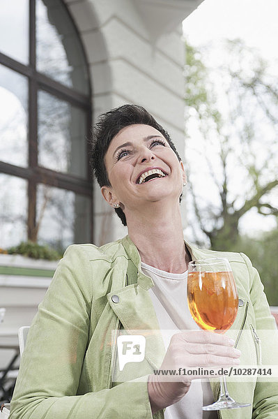 Mature woman laughing with aperol spritzat at sidewalk cafe  Bavaria  Germany Mature woman laughing with aperol spritzat at sidewalk cafe, Bavaria, Germany
