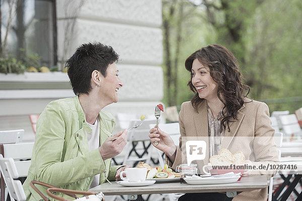 Two friends having breakfast in sidewalk cafe  Bavaria  Germany