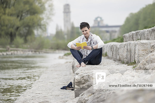 Mature woman sitting on steps and reading book  Bavaria  Germany
