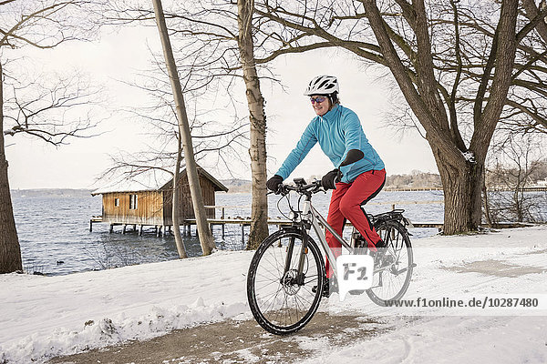 Mature woman riding bicycle on snow covered road  Bavaria  Germany