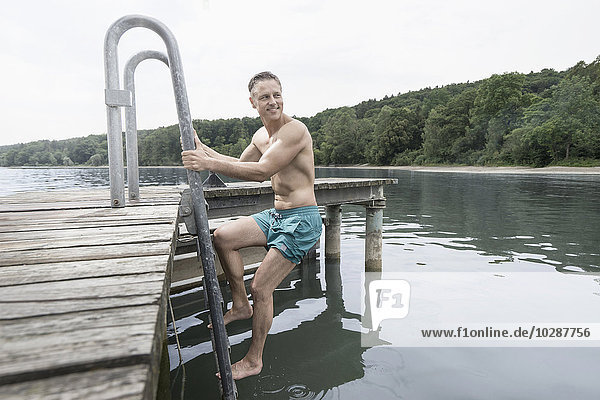Mature man climbing ladder of lake  Bavaria  Germany