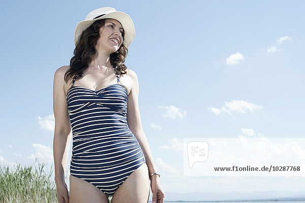 Mature woman walking in swimsuit at the lake  Bavaria  Germany Mature woman walking in swimsuit at the lake, Bavaria, Germany