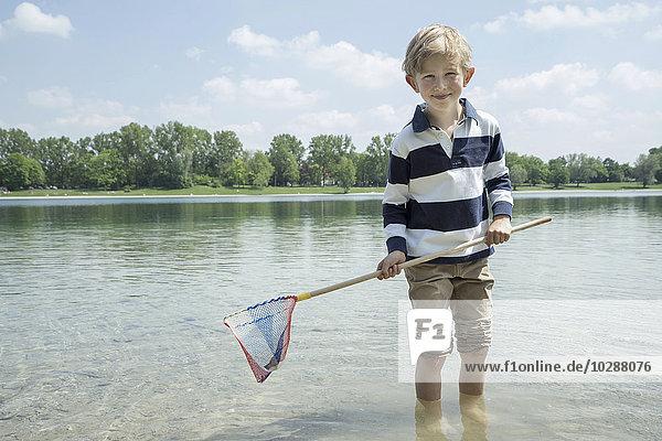Boy holding brailer in the lake  Bavaria  Germany