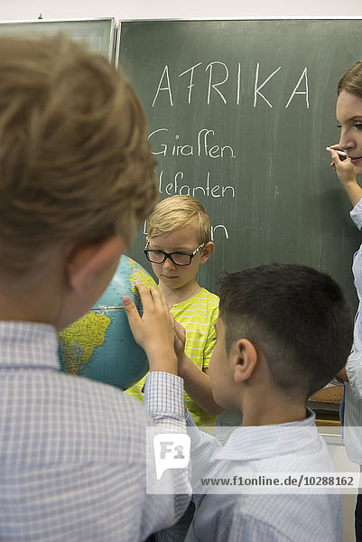 Female teacher and students looking at globe in classroom  Munich  Bavaria  Germany