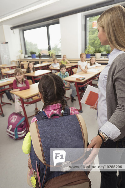 Female teacher introducing a new classmate in classroom  Munich  Bavaria  Germany