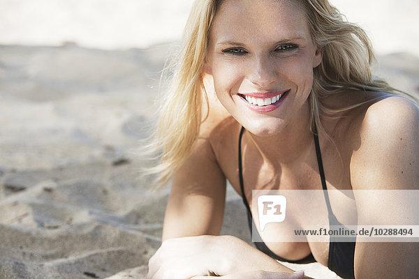 Costa Rica  Santa Teresa  Portrait einer attraktiven jungen Frau am Strand liegend