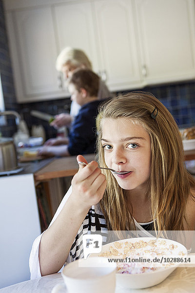Portrait of girl (12-13) eating breakfast