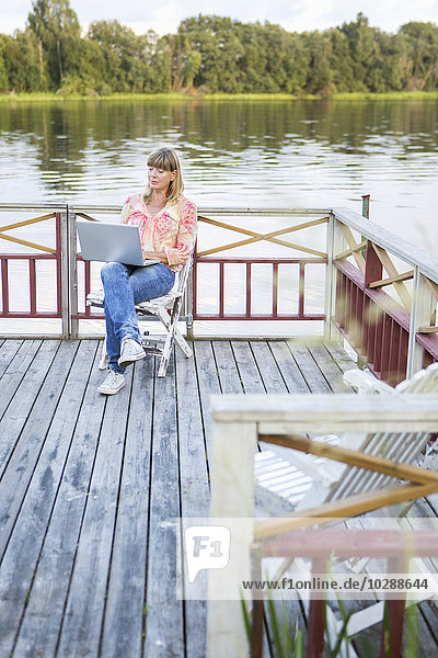 Schweden  Dalarna  Borlange  Frau bei der Arbeit am Laptop auf der Terrasse am Fluss