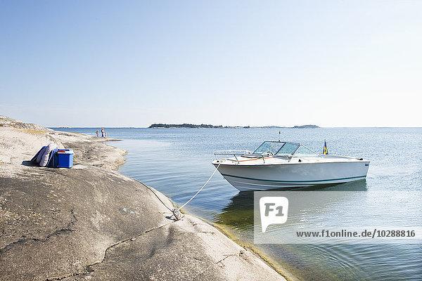 Schweden  Sodermanland  Stockholm Archipel  Varmdo  Moored Motorboot an sonnigen Tagen und Touristen (4-5  12-13) im Hintergrund.