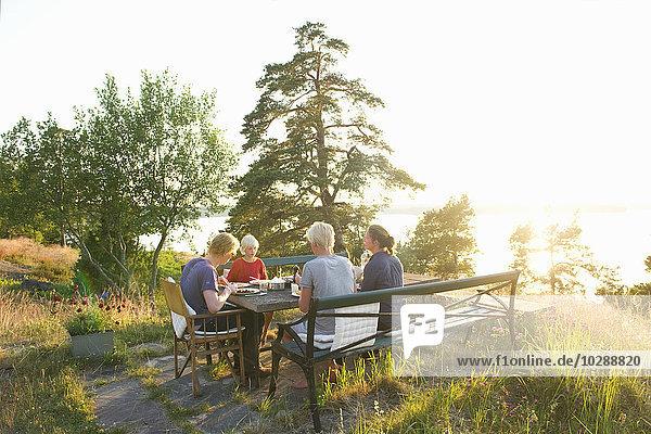Schweden  Sodermanland  Stockholm Archipel  Haninge  Dalaro  Familie (12-13) beim Abendessen im Garten