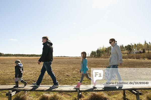 Schweden  Ostergotland  Familie mit zwei Kindern (4-5  6-7)  die auf einer Strandpromenade laufen.