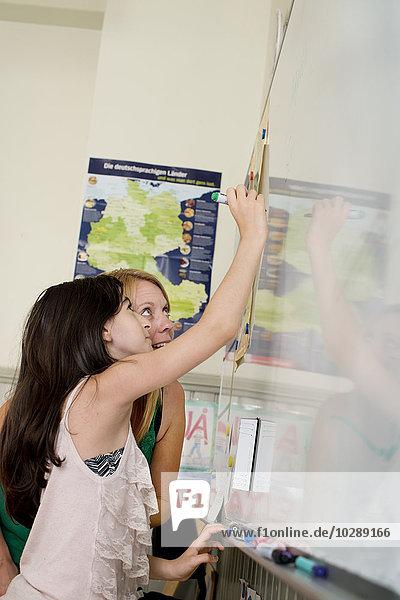 Schweden  Vastra Gotland  Student (10-11) beim Schreiben auf Whiteboard
