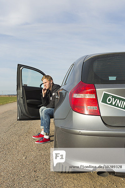Sweden  Ostergotland  Young man sitting in car