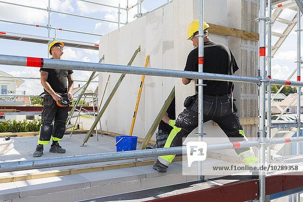 Schweden  Ostergotland  Linkoping  Bauarbeiter  die Bausteine für den Mauerbau vorbereiten
