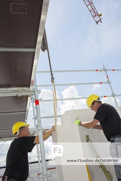 Sweden  Ostergotland  Linkoping  Construction workers adjusting blocks on construction site