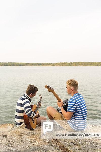 Schweden  Ostergotland  Tjust Archipelago  Kaggebo  Zwei junge Männer  die am Meer sitzen und Gitarren spielen
