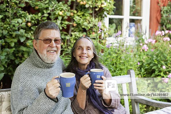 Schweden  Vastergotland  Tarby  Seniorenpaar beim Kaffeetrinken im Garten