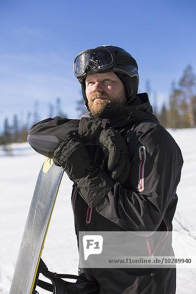 Sweden  Harjedalen  Vemdalen  Man walking with snowboard in forest