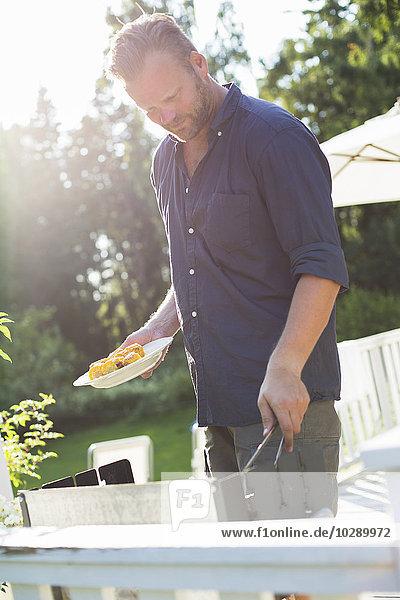 Sweden  Stockholm Archipelago  Grasko  Man preparing grilled corn