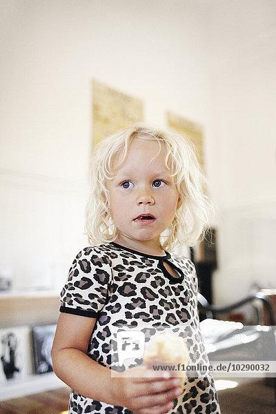 Sweden  Portrait of blond girl (4-5) eating sweet bun