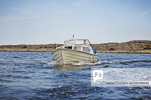 Schweden  Vastra Gotaland  Göteborg Archipel  Styrso  Man driving yacht on lake