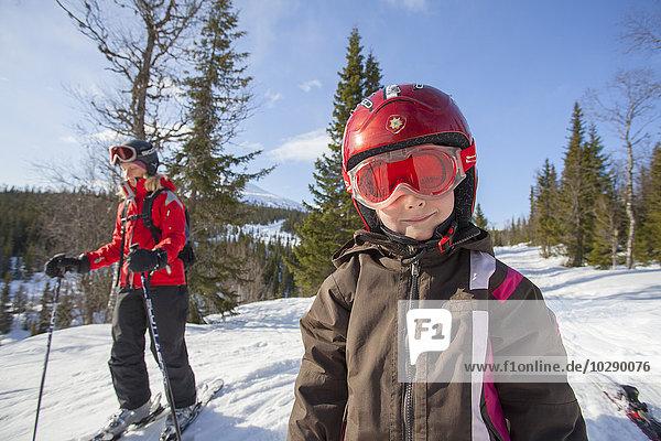 Norwegen  Osterdalen  Trysil  Portrait des lächelnden Mädchens (4-5) auf der Skipiste stehend