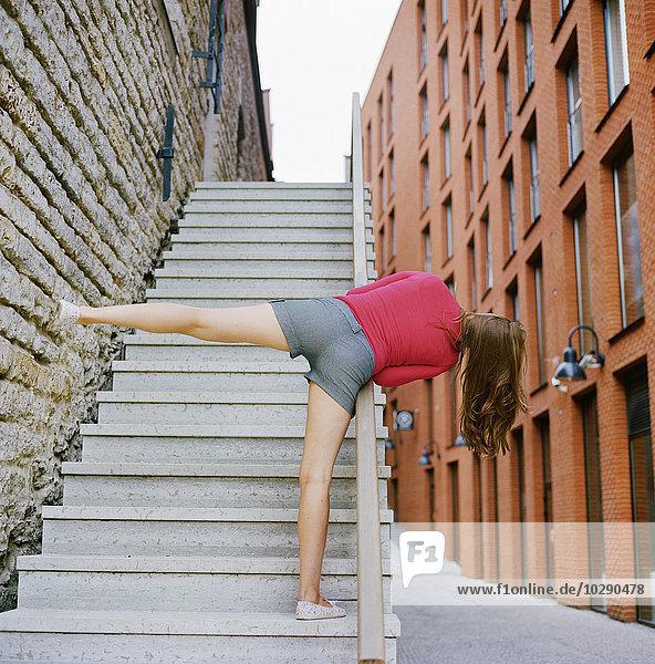 Estland  Tallinn  Rotermann  Rückansicht der Frau auf einer Treppe stehend mit erhobenem Bein