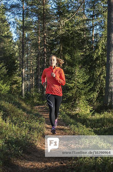 Finland  Pohjanmaa  Pietarsaari  Faboda  Young woman jogging in forest