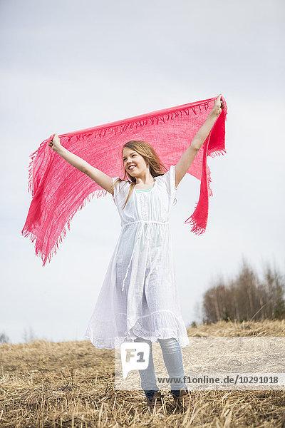 Finnland  Keski-Suomi  Aanekoski  Lächelndes Mädchen (12-13) mit rosa Schal im Feld stehend Finnland, Keski-Suomi, Aanekoski, Lächelndes Mädchen (12-13) mit rosa Schal im Feld stehend
