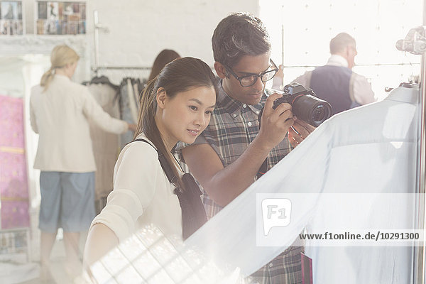 Photographer and fashion designer examining clothing